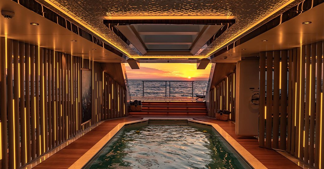 pool on superyacht tatiana, with sunset view in background