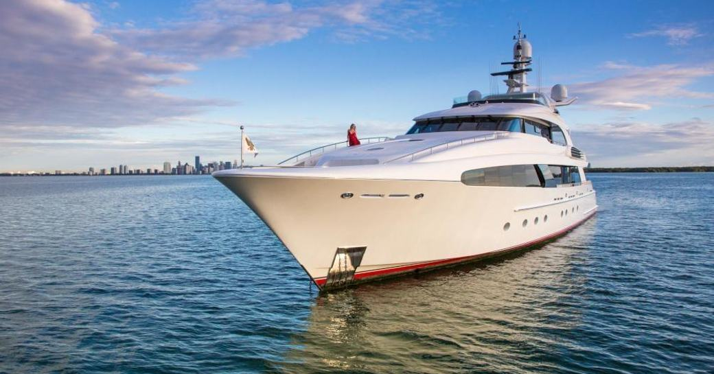 Superyacht USHER with a charter guest relaxing on her bow