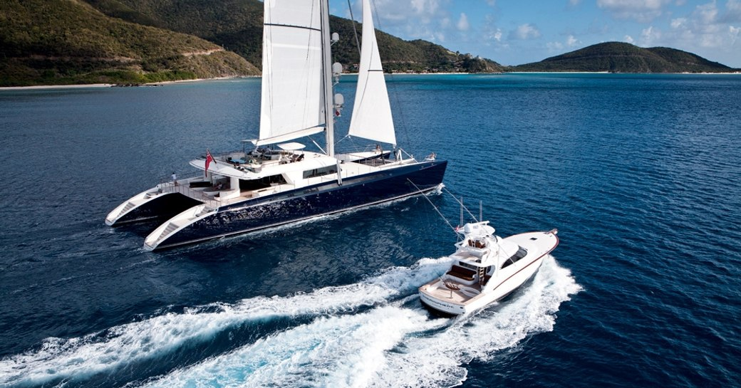 luxury catamaran HEMISPHERE docks in exotic cruising grounds as her tender zips past