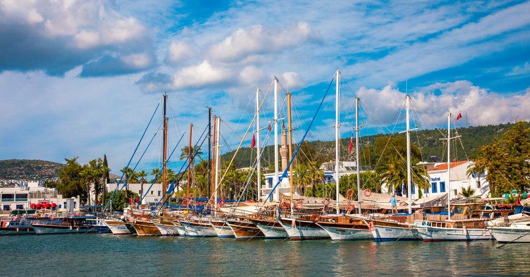 Sailing yachts moored at Yalikavak Marina, Bodrum, Turkey, surrounded by sea.