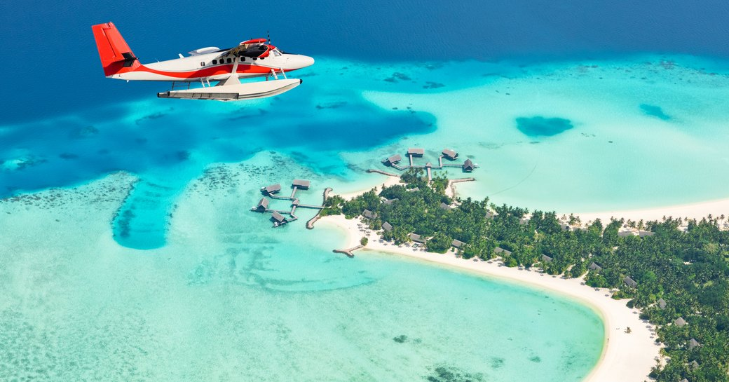 Seaplane exploring aerial views of Maldives, surrounded by island below and aquamarine waters