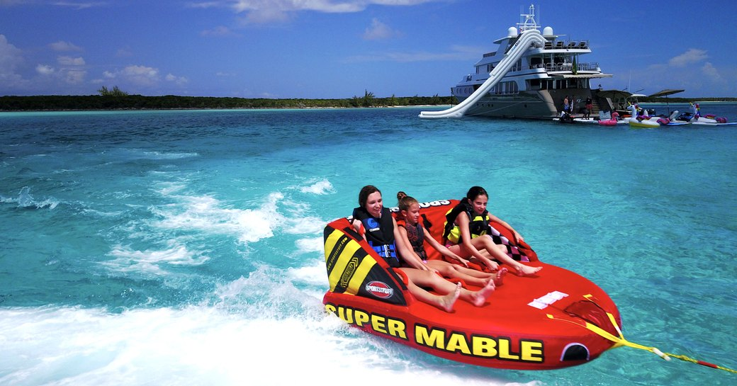 luxury yacht loon and her inflatable toys, charter guests enjoying water fun in the bahamas