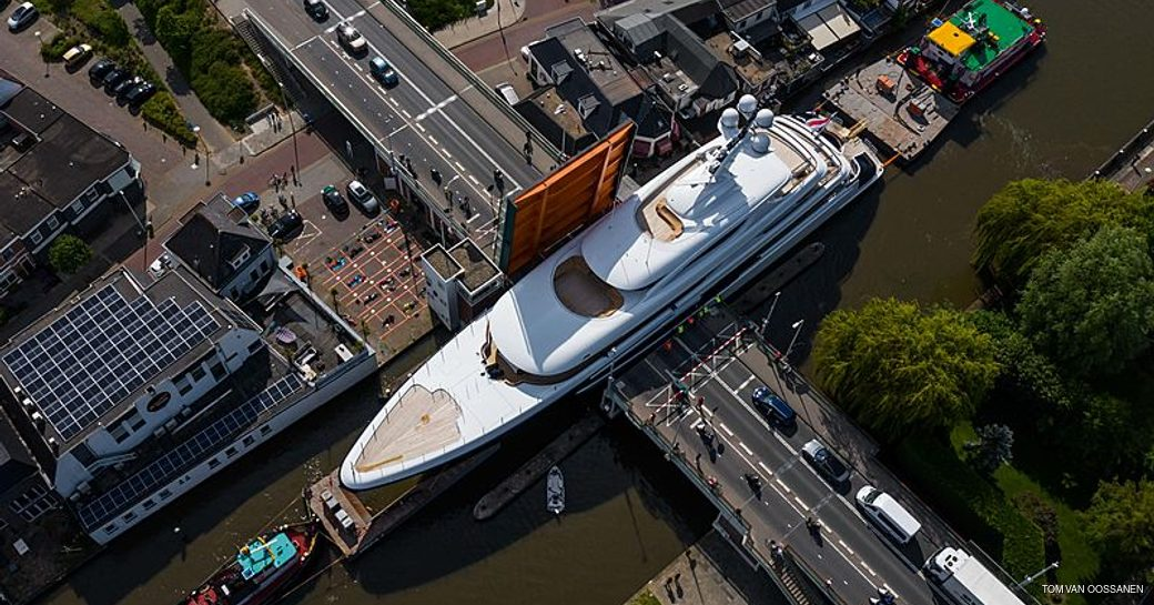 aerial image of luxury yacht podium squeezing through gap in canal