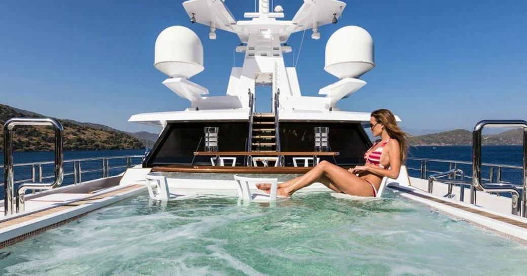A female charter guest sits at a swim-up bar in the pool on board a superyacht