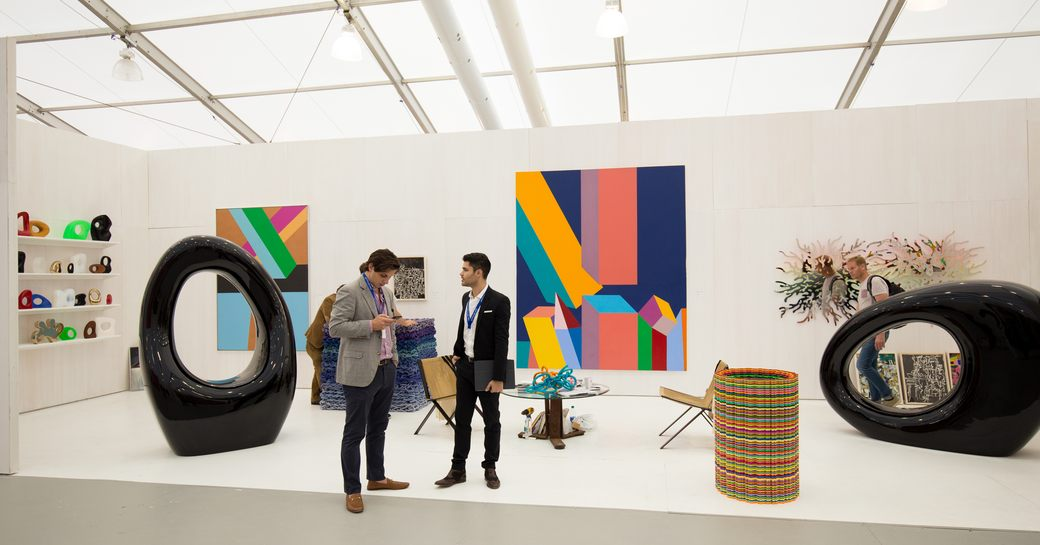 Landscape view of Art Basel Miami gallery, two visitors discussing exhibit in foreground.
