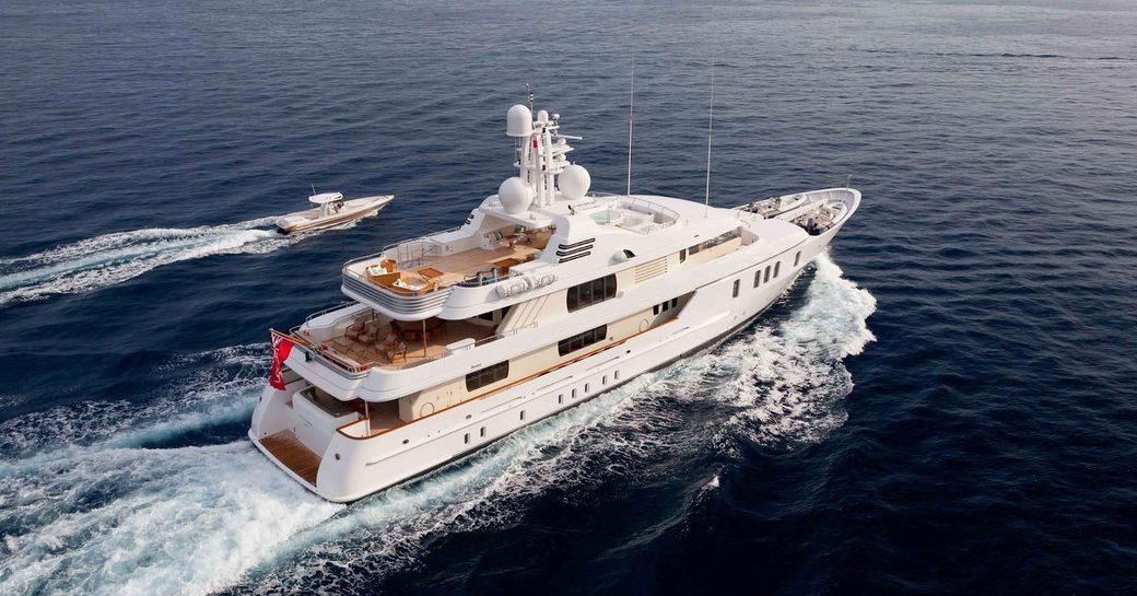 luxury yacht HANIKON cruises on a charter vacation alongside tender