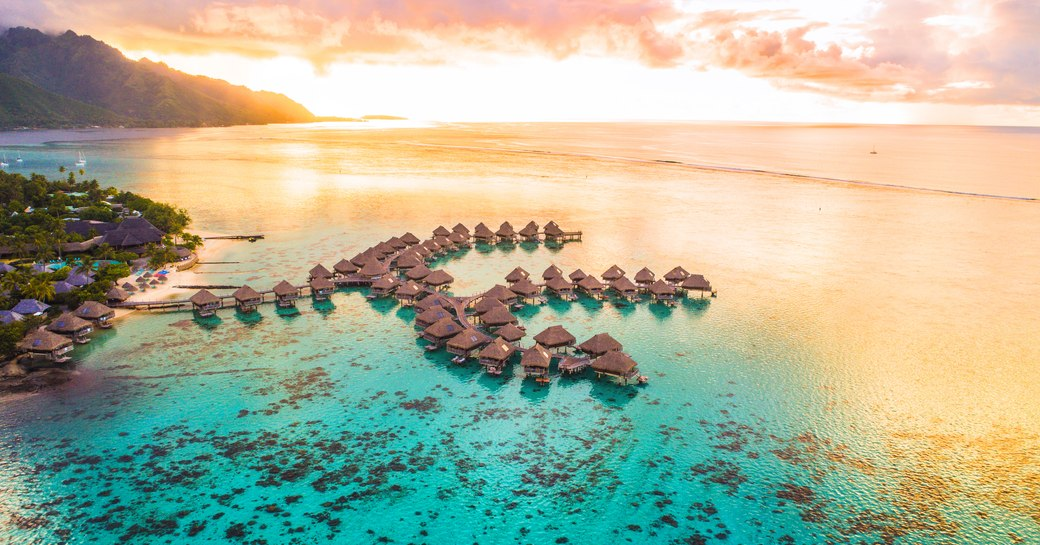 resort cabins perch on the still and tranquil waters of tahiti giving luxury yacht charter guests a relaxing space to unwind