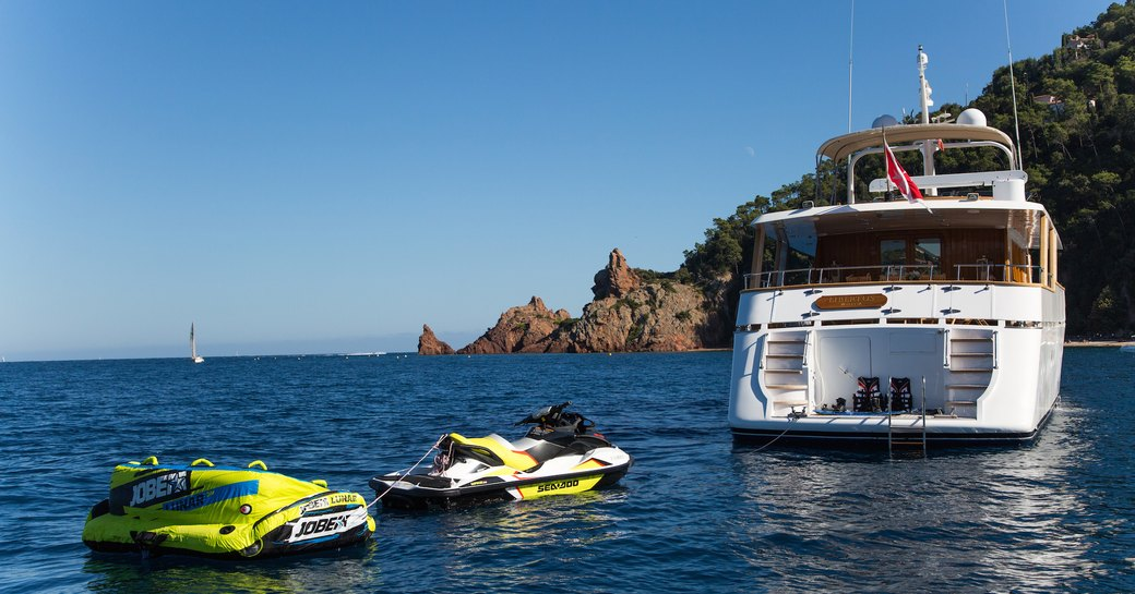 View of the stern of luxury yacht LIBERTUS alongside water toys