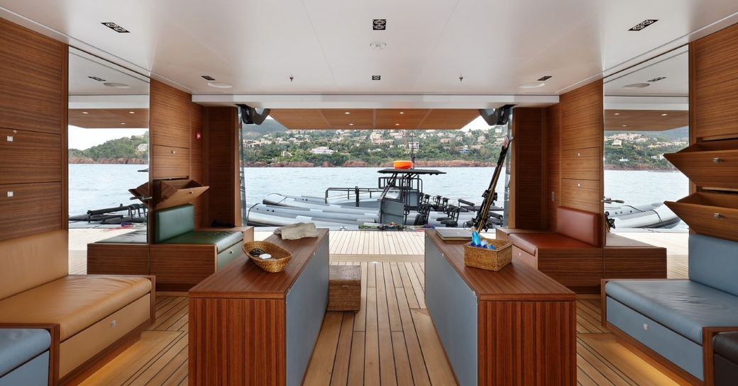 teak-clad beach club looking out onto tender on water aboard superyacht Planet Nine