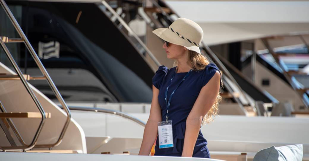 Landscape view of female charter guest onboard yacht at FLIBS, other yachts moored in background.