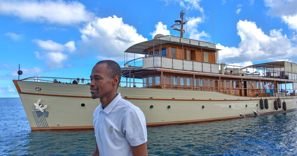 man on tender infront of luxury yacht over the rainbow, at anchor near thanda island