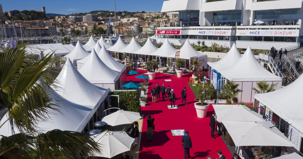 Display of exhibition tents along red carpet at Cannes MIPIM, visitors walking along the carpet.