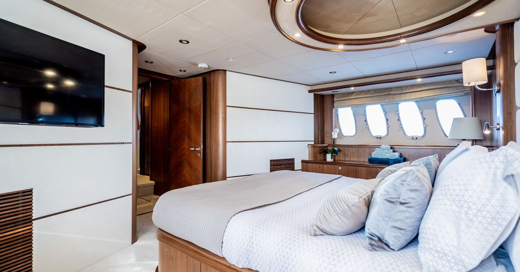 luxury yacht chess master suite with white carpets and wide windows