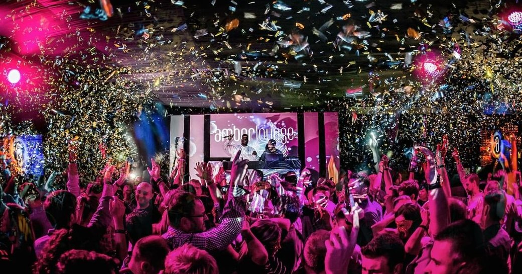 people dancing at amber lounge monaco, with confetti falling on crowds