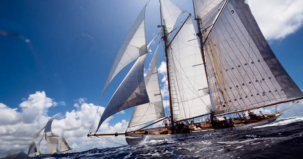 two competing yachts cut through the water at the Antigua Classic Yacht Regatta