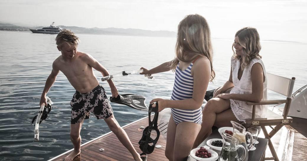 children on swim platform get ready to go snorkeling as parent watches aboard motor yacht CRISTOBAL