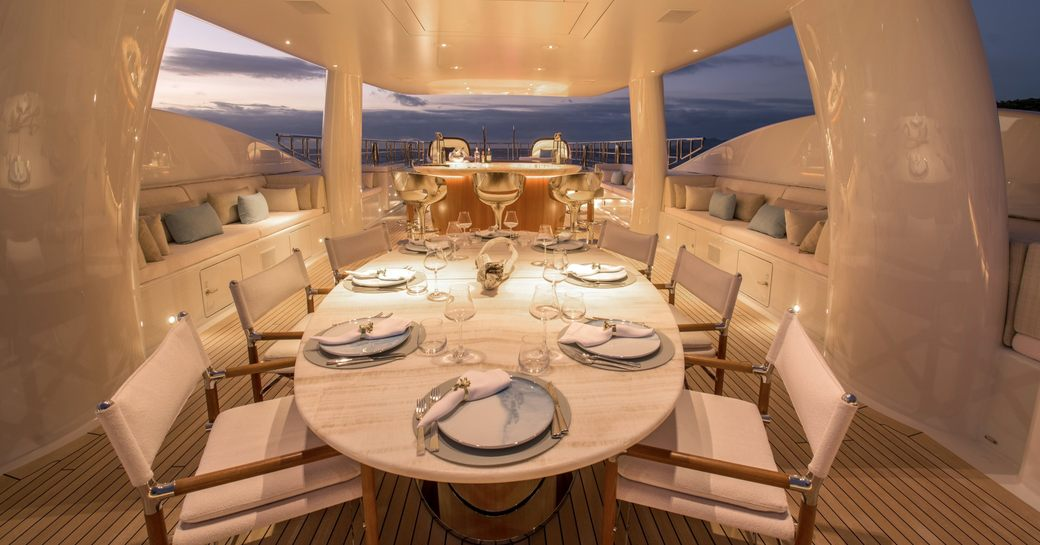 Superyacht DRIFTWOOD sun deck at night with dining table and jacuzzi beyond