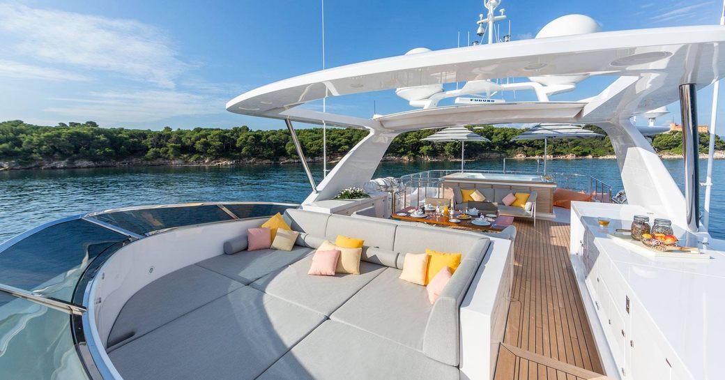 sunpads and dining table beyond on sundeck of luxury yacht DYNAR