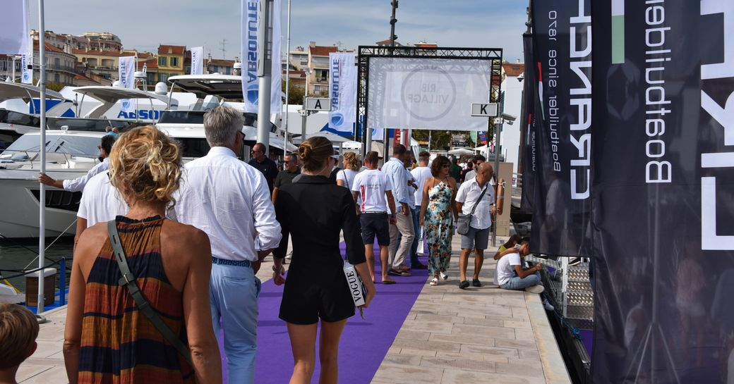 woman walks along the harbour during cannes yachting festival, alongside yachts