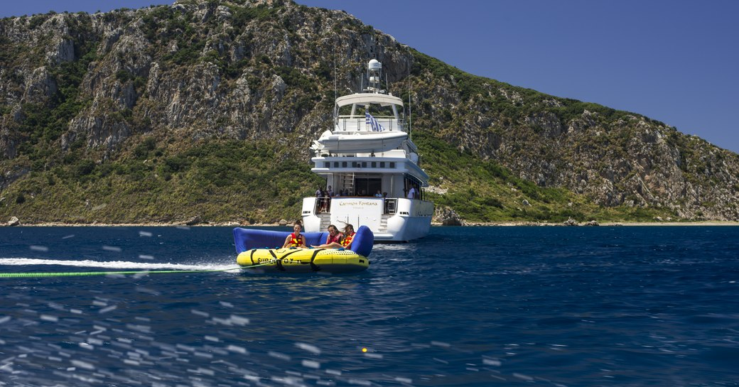 guests riding an inflatable raft being chauffeured by crewed yacht carmen fontana's speed boat