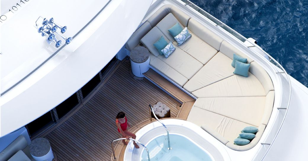 An aerial image which shows a model entering the Jacuzzi on the sundeck of a superyacht