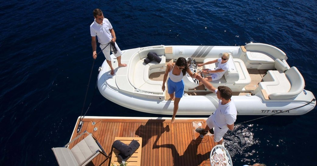 charter guest steps on board superyacht via swim platform, aerial view