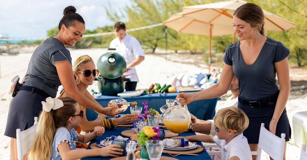 yacht crew serve food during beach picnic on charter vacation