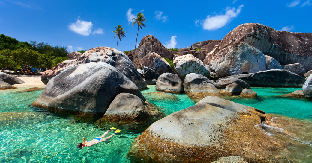 Boulder beach in the Virgin Islands, with crystal-clear seas and palm trees in background