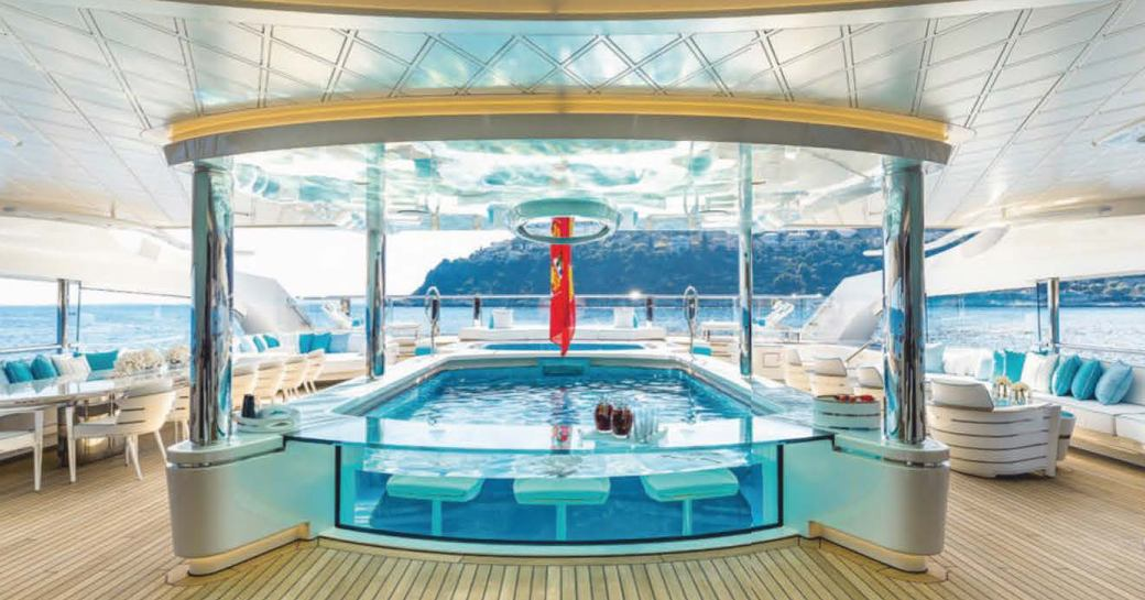 bright and airy shot of designer swimming pool surrounded by off white and cream couture seating on charter yacht Lady S