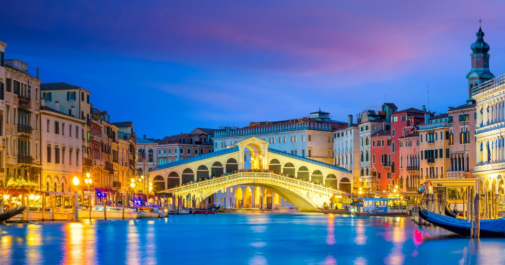 Picture taken from the centre of the grand canal, the rialto bridge in the background. Restaurants and shops line the streets at night in Venice