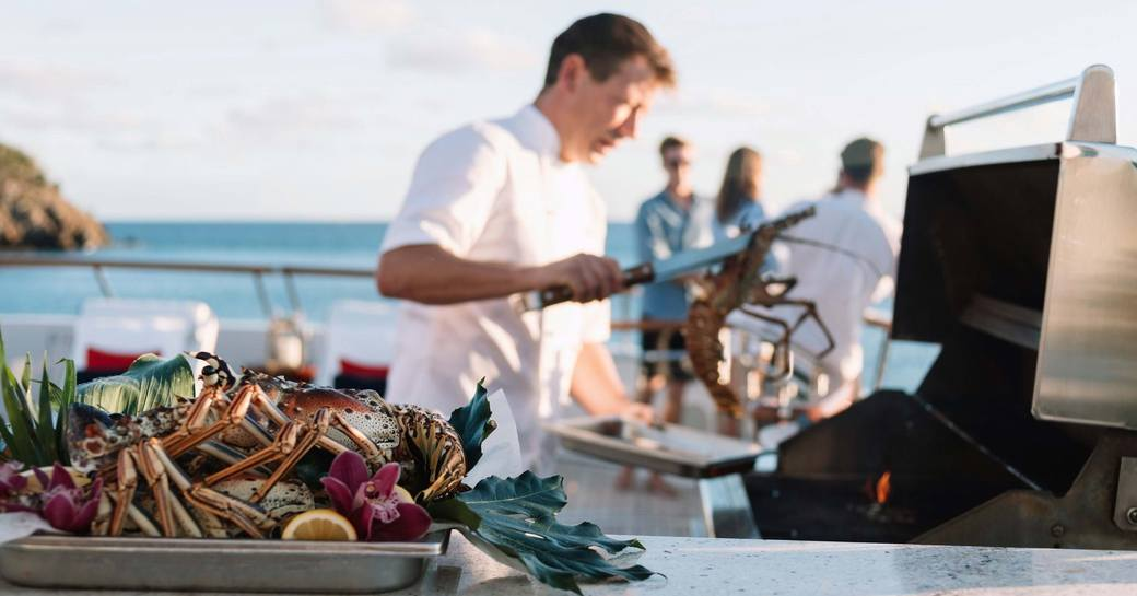 A chef cooking at a BBQ onboard a yacht