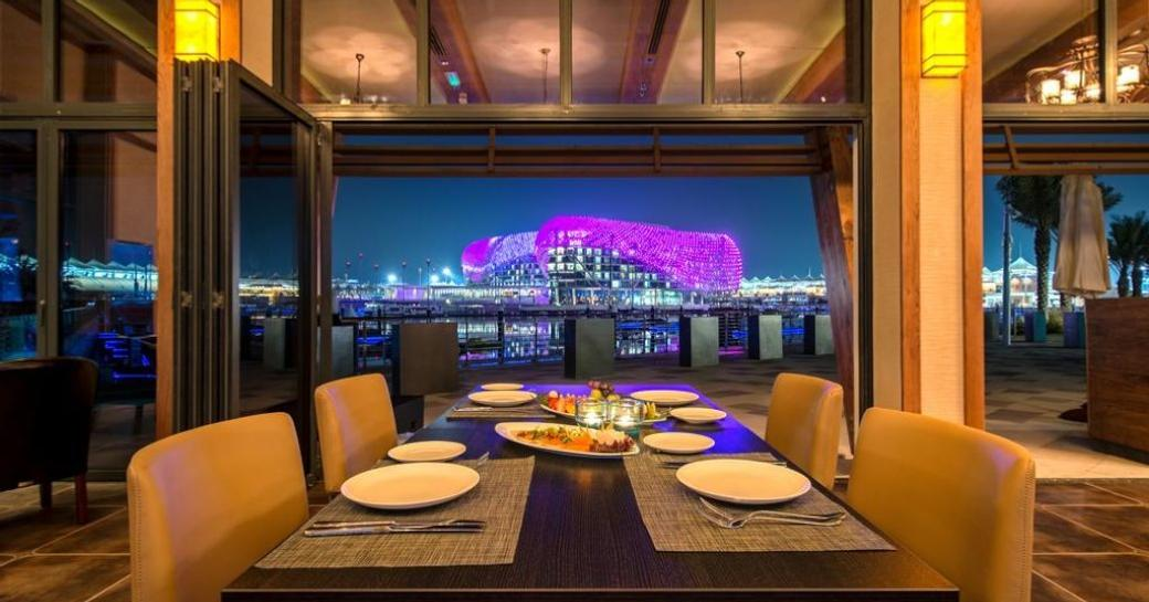 Image looking down table at Aquarium, with views over terrace and Yas Viceroy Hotel lit up at night