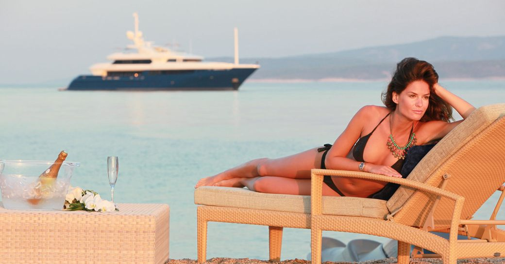 charter guest relaxes on the beach with superyacht Mary-Jean II anchored in the distance