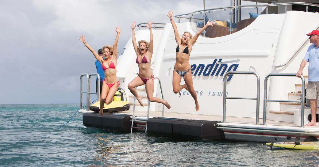 three charter guests jump of the swim platform on luxury yacht TRENDING