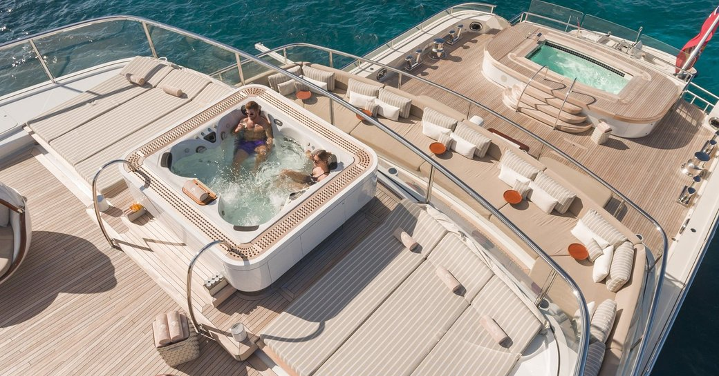 guests relax in the sundeck spa pool with aft section of decks below on show on board superyacht NAUTILUS