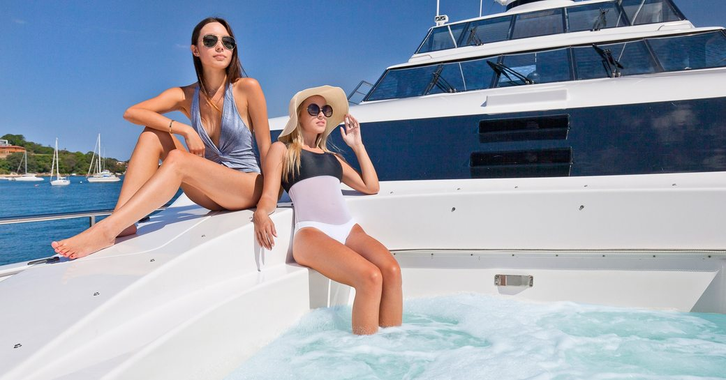 charter guests relax in spa pool on foredeck of superyacht Oscar II