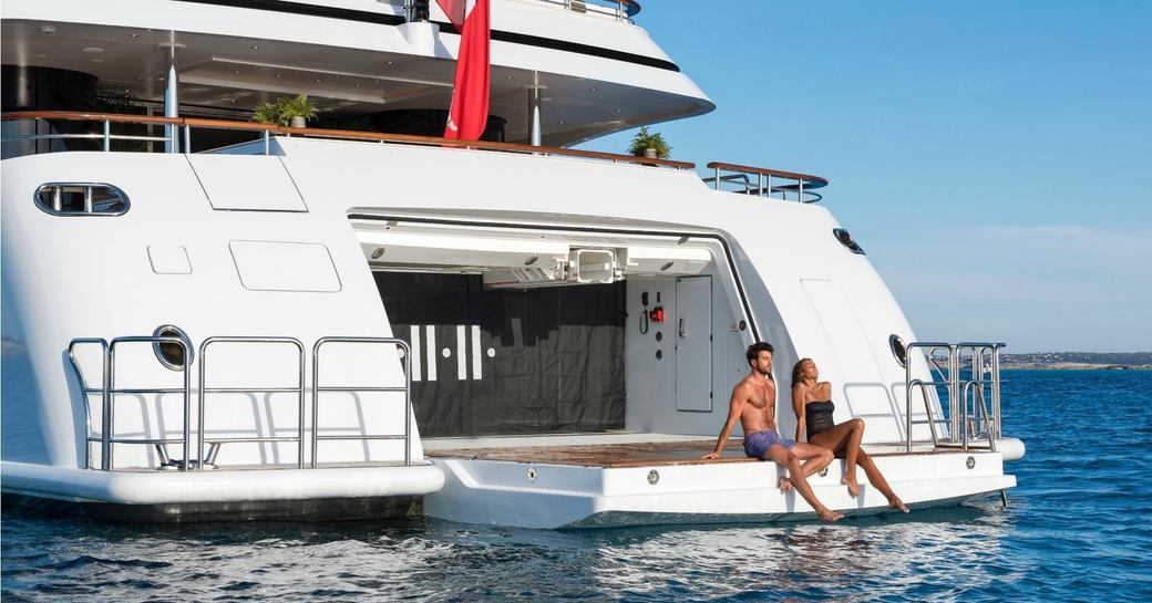 guests sit on the edge of the drop-down swim platform on board superyacht 11/11