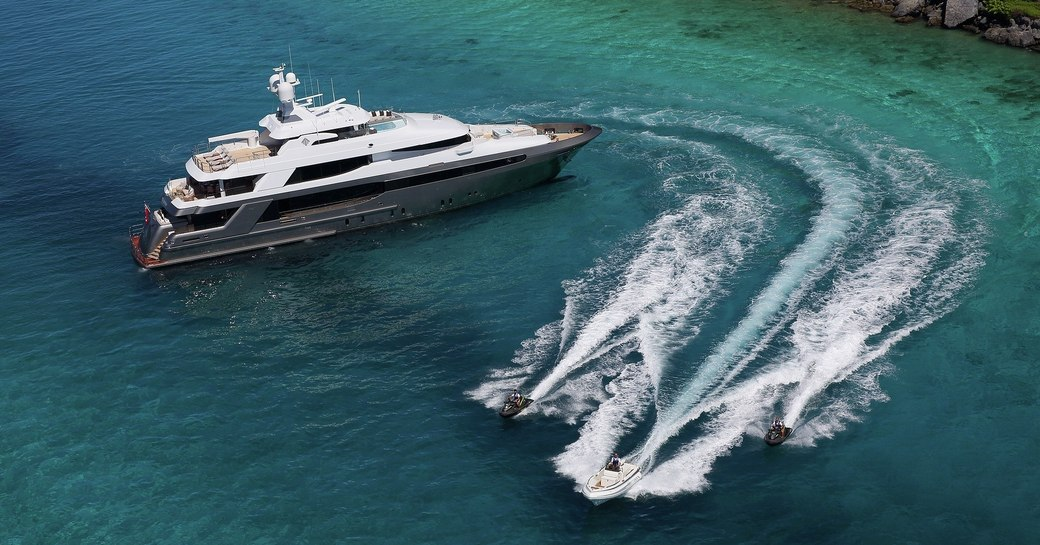 superyacht Muchos Mas at anchor as water toys take to the waters during a yacht charter