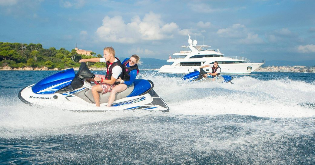 charter guests take to the jet skis as superyacht DYNAR anchors nearby