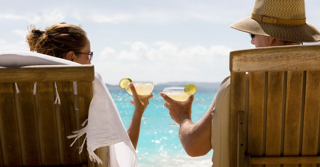 charter guests recline on chaise loungers and enjoy cocktails on beautiful white sand beach