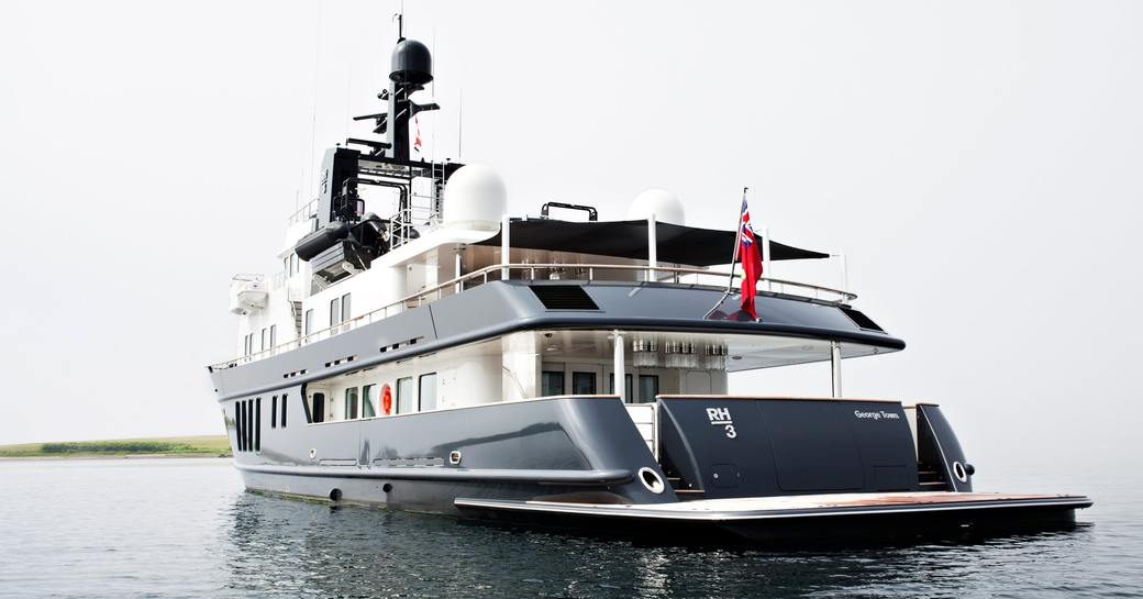 An image which shows the aft of a superyacht sat at-anchor