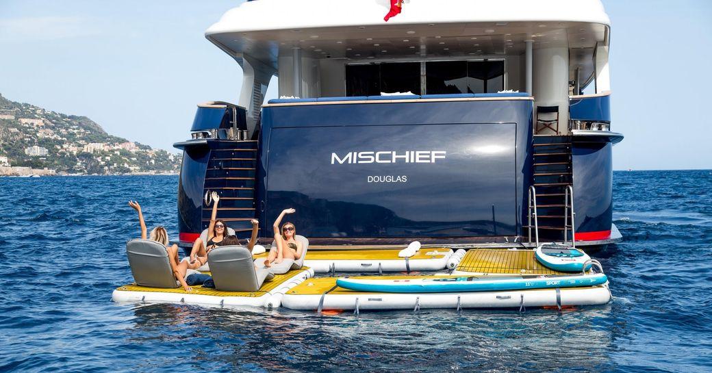 Charter guests unwind on the aft deck of superyacht MISCHIEF
