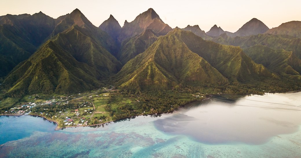 Aerial view of coral reef with The Mighty Mount Aorai in the back ground in Tahiti, French Polynesia