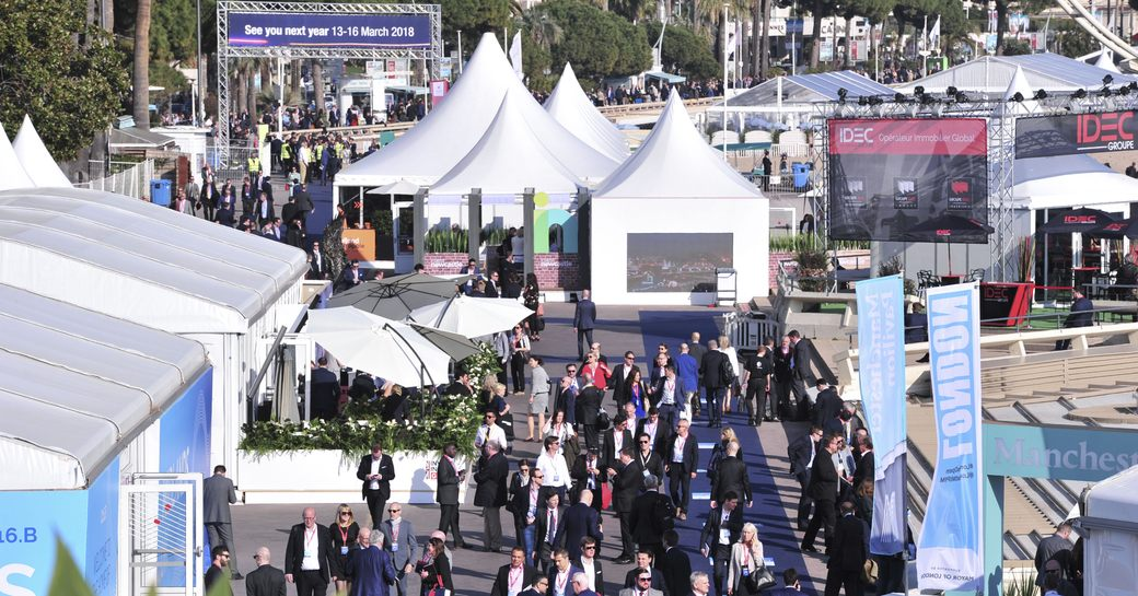 show-goers at MIPIM walk around the Palais de Festivals in Cannes