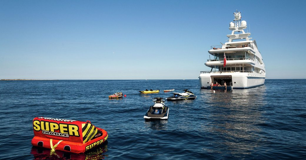 charter guests on the drop-down swim platform of motor yacht Lucky Lady as water toys are spread out across the waters