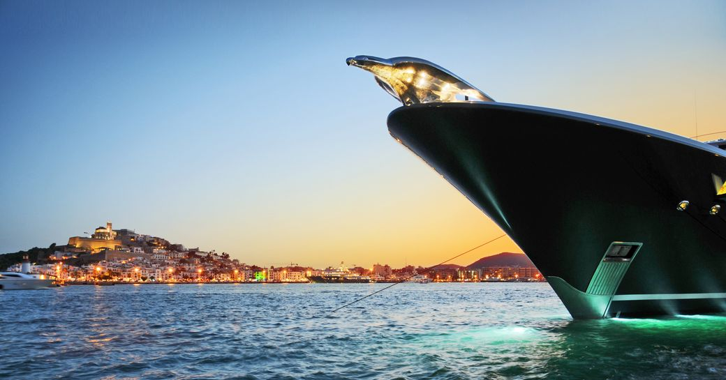Ibezia glows in the background of Lurssen's motor yacht Phoenix 2 as she cruises the Mediterranean