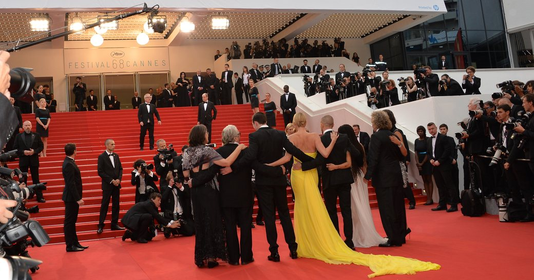 Line up of celebs facing Palais des Festivals during Cannes Film Festival photo call. Surrounded by photographers.