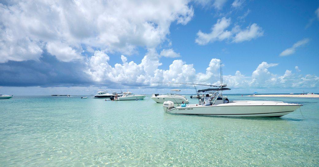 Several boats anchored off Gun Cay in shallow tropical waters in Bimini, Bahamas