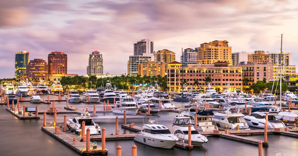 Overview of a Palm Beach marina at sunset, multiple motor yachts moored.