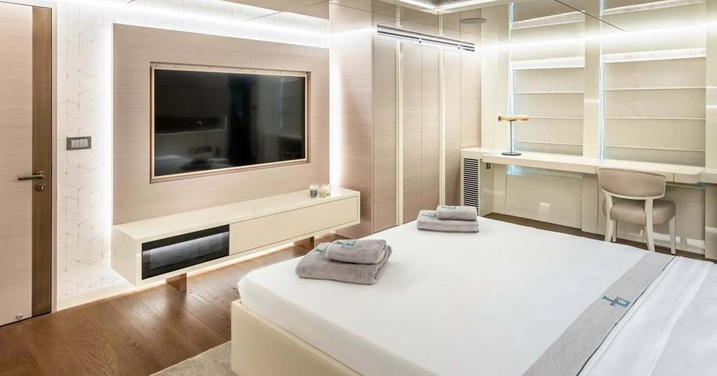 Lightly colored cabin on explorer yacht 'Seven Diamonds' with bed facing flat screen TV